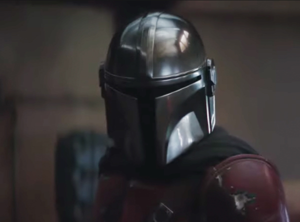 screen capture of The Mandalorian - Star wars character wearing face-covering helmet
