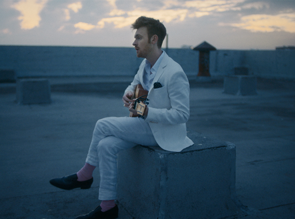 Finneas in a white suit sitting on a rooftop with guitar