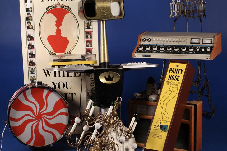 Photo of items from Jack White auction (drums, chandelier, amplifier, etc ) against blue background