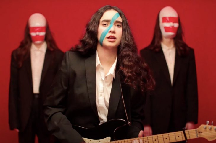 Francis of Delirium singer playing guitar in front of red backdrop