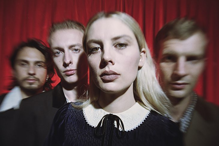 Photo of Wolf Alice members in front of red curtain