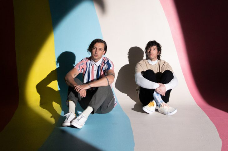 Picture of Josh Dun and Tyler Joseph sitting in a room of colorful stripes.