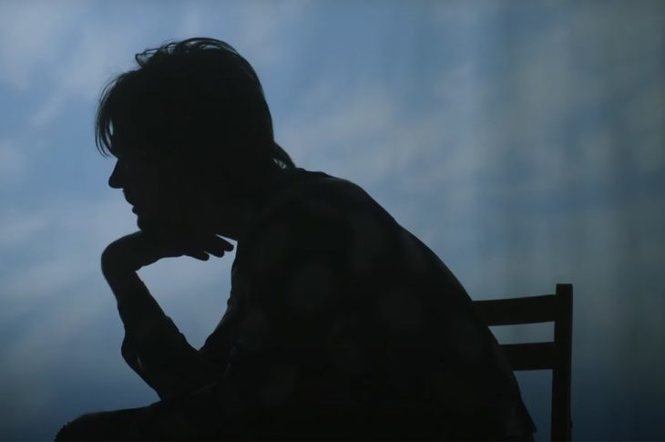 image from music video for The 90s by FINNEAS. Artist in silhouette sitting in a chair