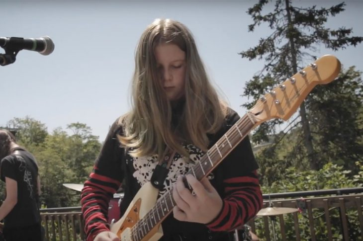 Young MAMM student playing electric guitar at an outdoor performance.