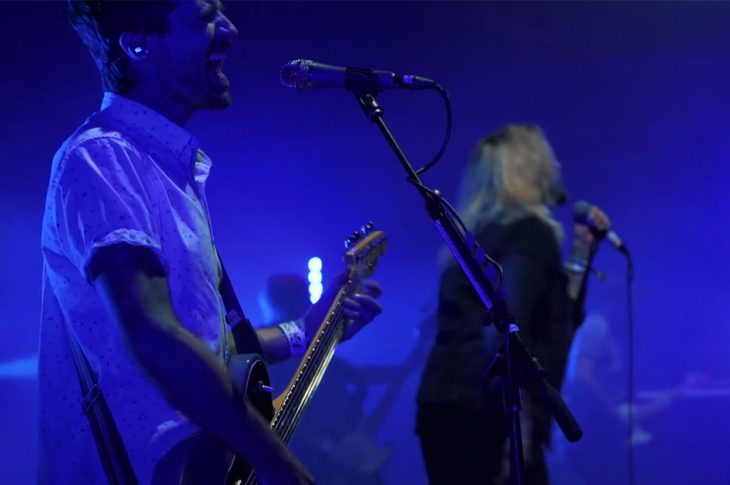 members of Taking Back Sunday performing on stage bathed in blue light